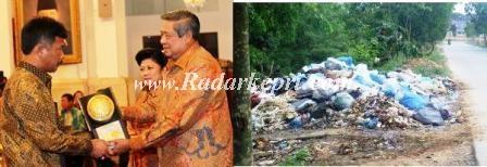Wakil Walikota Batam menerima Piala Adipura dari Presiden RI dan sampah yang berterbaran di bahu jalan.