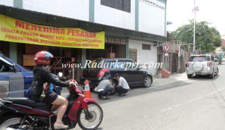 Petuasg Disihubkominfo sedang menggembok mobil sedan di Jl Teratai.