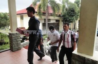Tersangka Gustian Bayu (baju putih) ketika digiring polisi ke Mapolresta Tanjungpinang.