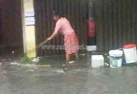 Ny Aeng, warga Jl Tambak sedang menguras air yang masuk ke rukonya akibat banjir