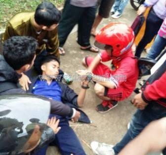 Rahmar Berlian (baju biru) yang pingsan di tratoar akibat motornya ditabrak dari belakang, Sabtu (23/05) sore.